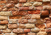 ruined red brick wall background of a rustic abandoned building