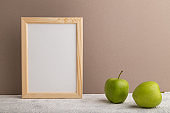 White wooden frame mockup with green apple on beige paper background. Blank, vertical orientation, still life, copy space.