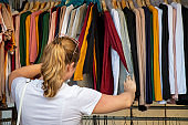 woman chooses clothes going through the broadcaster in the store at the market