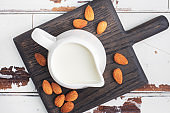 Almond milk in ceramic milk jug on a gray background. Copy space.