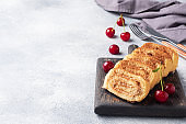 Dessert sponge roll with chocolate cream with cherries on a wooden cutting Board. Copy space.