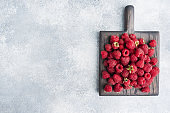 A pile of fresh juicy raspberries on a wooden Board, copy space.