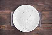 Empty white plate on wooden rustic background. Top view with copy space.
