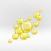 Gold serum oil droplets isolated on greyish background. Yellow collagen bubbles with sparkles and lights composition. Golden emulsion with reflection.