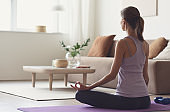 Woman doing fitness exercise, practicing yoga, girl meditating at home