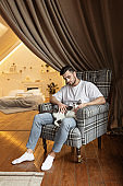 young man on the chair with his cat. Home pets. Lifestyle. Stay at home during coronavirus quarantine covid-19