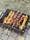 chicken and pork kebabs are fried on the grill outdoor