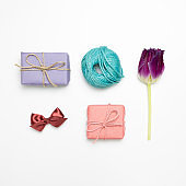 Gift boxes, string, tulip flower, ribbon on white background. flat lay, top view, copy space