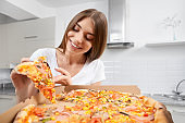 Young woman holding big pizza and eating piece.
