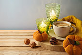 Autumn season hygge concept woth coffee cup, candles and pumpkin decoration