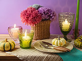 Thanksgiving holiday table decoration with plate, candles and pumpkin over purple background