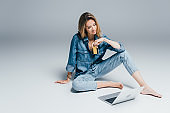 barefoot woman in denim shirt and jeans holding credit card while sitting on grey near laptop