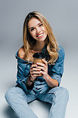 happy young woman in denim clothes, with naked shoulder, holding coffee to go while sitting on grey