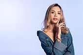 young, seductive woman in denim shirt touching face while looking at camera isolated on blue