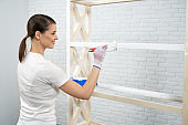 Smiling woman painting wooden rack in white color