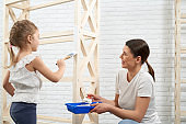 Mother and daughter painting wooden storage stand
