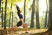 Active female doing stretching exercises for body outdoors