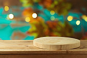 Empty wooden log on rustic table over blurred autumn leaves background.  Thanksgiving or Halloween holiday  mock up for design and product display.