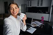 Woman holding cup of tea and taking selfie on smartphone