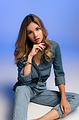seductive young woman in denim clothes holding hand near face while posing on blue