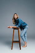 sensual woman in denim shirt and jeans leaning on high stool on grey
