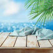 Empty wooden table with tablecloth over tropical beach bokeh background.  Summer mock up for design and product display.