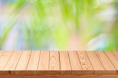 Empty wooden table over palm tree blurred background.  Summer tropical nature mock up for design and product display.