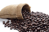 Coffee beans from full sack scattered on white background