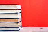 Stack of books on bookshelf in Library. Back to School education concept on red background. Open hardback book on wooden desk table.