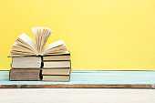 Books on wooden desk table and abstract yellow background. Education background. Copy Space. Back to school.