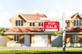 Houses for sale, red sign in front of blurred modern big building on grass
