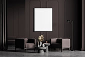 Modern living room interior with concrete floor, furniture, table and armchairs. Home architecture concept. A poster canvas on white wall. Mock up. No people.
