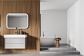 White and wooden bathroom interior with sink and mirror, bathtub with towels
