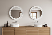 Light bathroom interior with two sinks and bath accessories