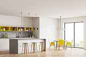 White kitchen interior with table and chairs near window, parquet floor