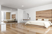 Bed and linens in wooden bedroom with mirror and parquet