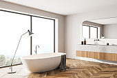 Bathroom interior with bathtub and sink with window on countryside