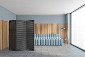 Blue sofa in wooden living room on grey tiled floor near window