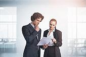 Two business people young professionals working with papers at modern office with panoramic windows. Teamwork, meeting and consulting. Concept of finance and banking