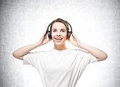 Smiling young woman wearing headphones, mockup empty wall