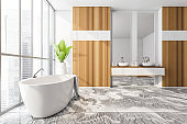 White bathtub and sinks with mirror, city view