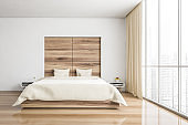 Bed and linens in wooden bedroom with parquet and window