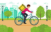 Concept delivery of goods and food. Courier rides Bicycle through the city Park.