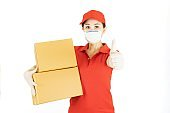 Delivery woman employee in red cap blank t-shirt uniform face mask gloves hold empty cardboard box isolated on white background studio Service quarantine pandemic coronavirus virus 2019-ncov concept
