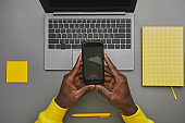 African Man Holding Phone at Workplace Flat Lay