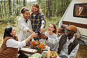 Group of Friends Dining Outdoors at Campsite
