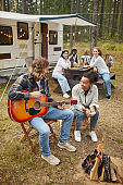 Friends Playing Guitar at Campsite