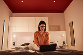 Businesswoman Working with Laptop on Bed