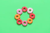 Glazed donuts top view. Multicolored doughnuts isolated on green background