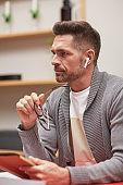 Modern Mature Man with Wireless Earphones